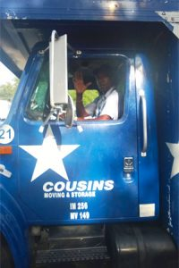 Cousins USA mover waving from moving truck