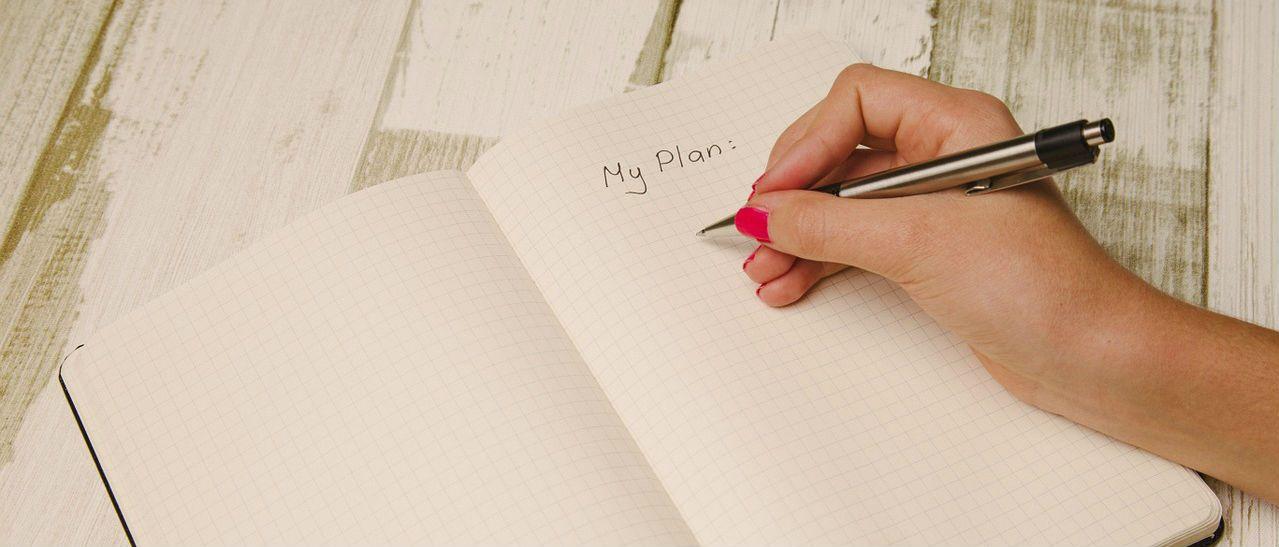 women writing a plan in a journal