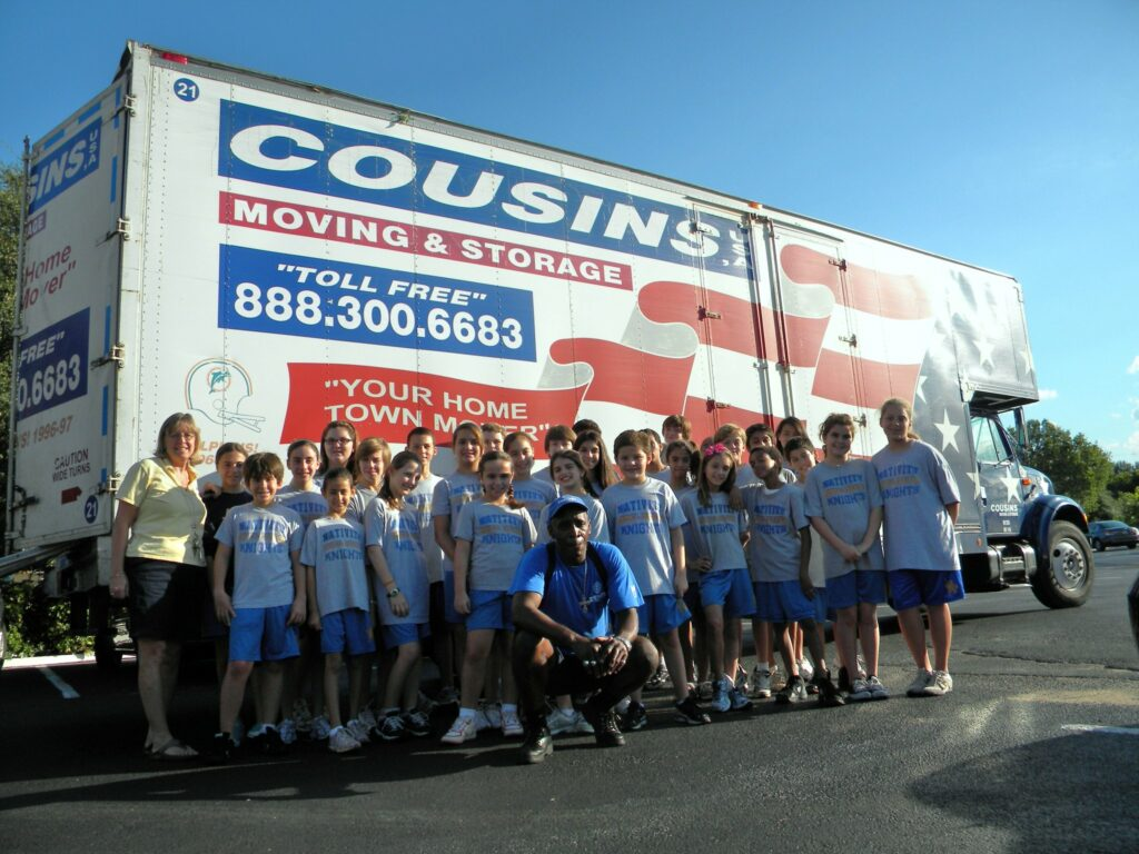 a group of schoolchildren post in front of a Cousins USA moving truck with a worker