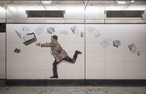 a mosaic tile art display showing a man with an open briefcase and papers flying about