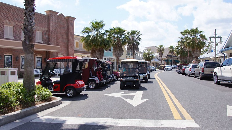golf carts parked along the street in a Florida town with palm trees